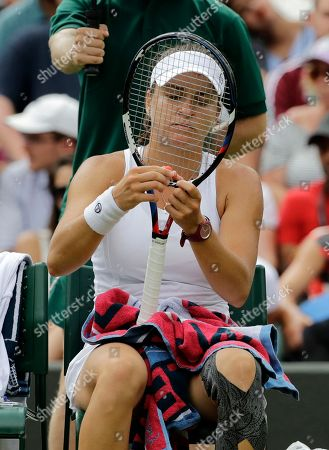 Alexandra Dulgheru of Romania looks at her racquet strings during a game break in the women's singles match against Venus Williams of the US on the third day at the Wimbledon Tennis Championships in London