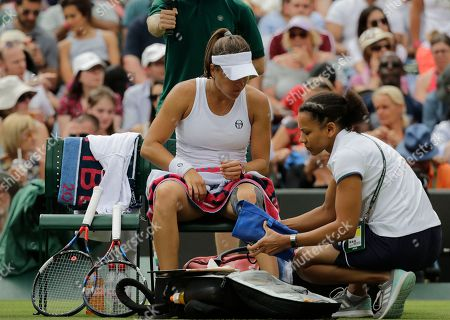 Alexandra Dulgheru of Romania receives treatment to her leg during the women's singles match against Venus Williams of the US on the third day at the Wimbledon Tennis Championships in London
