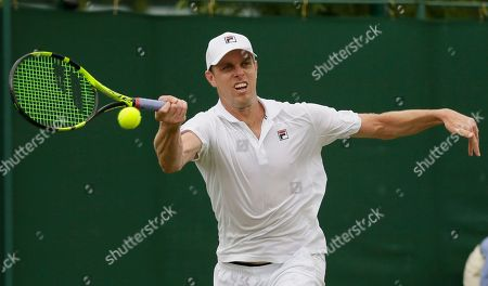 Sam Querrey of the US returns a ball to Sergiy Stakhovsky of Ukraine during their men's singles match on the third day at the Wimbledon Tennis Championships in London