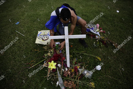 Stock Image of A man deposits offerings on a cross symbolizing deaths during the protests, in Managua, Nicaragua, 04 July 2018. Since past 18 April Nicaragua is going through a socio-political crisis that has left 310 dead in protests against President Daniel Ortega and wife Rosa Murillo after eleven years in power, under accusations of abuse and corruption.