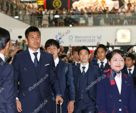Eiji Kawashima, Shinji Kagaw. Japanese soccer team players, Eiji Kawashima, left, Shinji Kagawa, center, and other teammates acknowledge cheering of fans upon their team's return from the World Cup in Russia, at Narita International Airport in Narita, near Tokyo
