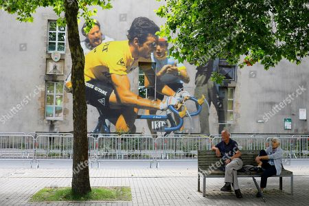 People wait on a bench by a mural depicting former French rider Bernard Hinault prior to the opening ceremony of the 105th edition of the Tour de France 2018 cycling race in La Roche-sur-Yon, France, 05 July 2018. The 105th edition of the Tour de France will start in Noirmoutier-en-l'Ile on 07 July 2018.