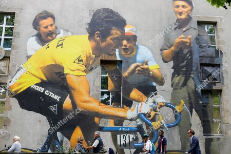People pass by a mural depicting former French rider Bernard Hinault prior to the opening ceremony of the 105th edition of the Tour de France 2018 cycling race in La Roche-sur-Yon, France, 05 July 2018. The 105th edition of the Tour de France will start in Noirmoutier-en-l'Ile on 07 July 2018.