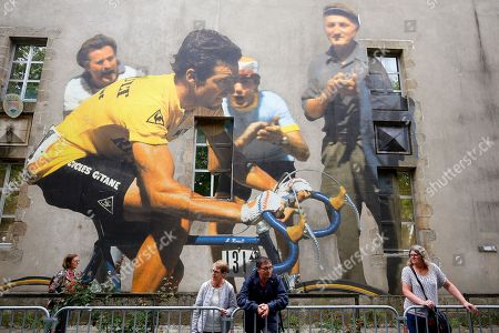 People stand in front of a mural depicting former French rider Bernard Hinault prior to the opening ceremony of the 105th edition of the Tour de France 2018 cycling race in La Roche-sur-Yon, France, 05 July 2018. The 105th edition of the Tour de France will start in Noirmoutier-en-l'Ile on 07 July 2018.
