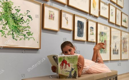 Young Eliza Manson, 9, poses with British cartoonist and illustrator Quentin Blake's work during a retrospective of Blake's work at Christie's auction house in London, Britain, 06 July 2018. The collection comprises of works from the past 40 years of Blake's career on display as part of Christie's 'Quentin Blake: A Retrospective; Forty Years of Alternative Version' preview exhibit.