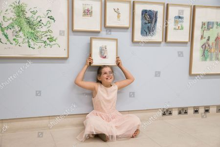 Child model Eliza Manson, 9 holding and observing Quentin Blake's illustrations.