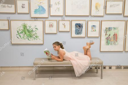Child model Eliza Manson, 9 reads the catalogue to Quentin Blakes: A Retrospective, 40 years of alternative versions at the Christie's Auction House in London