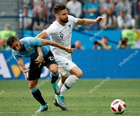 Olivier Giroud (R) of France and Jonathan Urretaviscaya of Uruguayy in action during the FIFA World Cup 2018 quarter final soccer match between Uruguay and France in Nizhny Novgorod, Russia, 06 July 2018. (RESTRICTIONS APPLY: Editorial Use Only, not used in association with any commercial entity - Images must not be used in any form of alert service or push service of any kind including via mobile alert services, downloads to mobile devices or MMS messaging - Images must appear as still images and must not emulate match action video footage - No alteration is made to, and no text or image is superimposed over, any published image which: (a) intentionally obscures or removes a sponsor identification image; or (b) adds or overlays the commercial identification of any third party which is not officially associated with the FIFA World Cup)