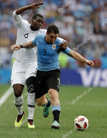 France's Paul Pogba, left, challenges Uruguay's Cristian Rodriguez during the quarterfinal match between Uruguay and France at the 2018 soccer World Cup in the Nizhny Novgorod Stadium, in Nizhny Novgorod, Russia