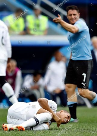 Uruguay's Cristian Rodriguez, rear, reacts as France's Kylian Mbappe, front, lies on the pitch during the quarterfinal match between Uruguay and France at the 2018 soccer World Cup in the Nizhny Novgorod Stadium, in Nizhny Novgorod, Russia,. France defeated Uruguay by 2-0