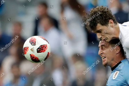 Benjamin Pavard, Cristian Rodriguez. France's Benjamin Pavard, top, and Uruguay's Cristian Rodriguez challenge for the ball during the quarterfinal match between Uruguay and France at the 2018 soccer World Cup in the Nizhny Novgorod Stadium, in Nizhny Novgorod, Russia