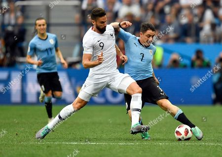 France's Olivier Giroud, left, is challenged by Uruguay's Cristian Rodriguez during the quarterfinal match between Uruguay and France at the 2018 soccer World Cup in the Nizhny Novgorod Stadium, in Nizhny Novgorod, Russia