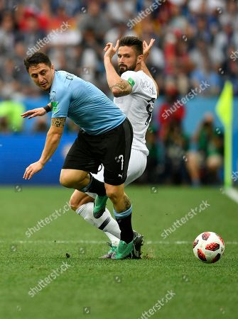 France's Olivier Giroud, right, is challenged by Uruguay's Cristian Rodriguez during the quarterfinal match between Uruguay and France at the 2018 soccer World Cup in the Nizhny Novgorod Stadium, in Nizhny Novgorod, Russia