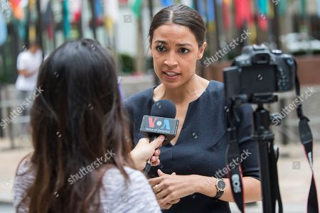 "Alexandria Ocasio-Cortez, a winner of a Democratic Congressional primary in New York speaks to a reporter, in New York. The 28-year-old political newcomer who upset U.S. Rep. Joe Crowley in New York's Democrat primary says she brings an ""urgency"" to the fight for working families"