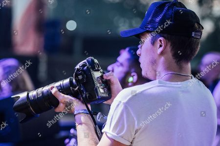 Brooklyn Beckham uses a camera lent to him by photographer Andrew Timms as J. Cole performs on stage