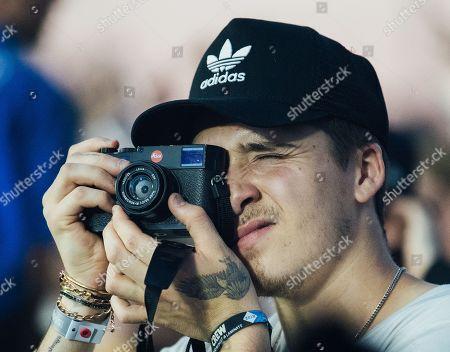 Brooklyn Beckham uses a leica camera as J. Cole performs on stage Brooklyn Beckham uses a leica camera as J. Cole performs on stage