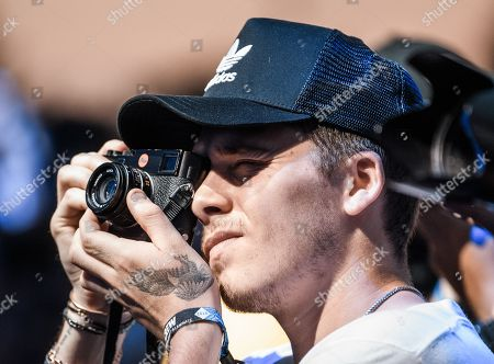 Brooklyn Beckham uses a leica camera as J. Cole performs on stage