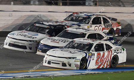 Justin Haley (24) crosses the yellow line as he passes Kyle Larson, center, and Elliott Sadler, left front, on the final lap of a NASCAR Xfinity Series auto race at Daytona International Speedway, in Daytona Beach, Fla