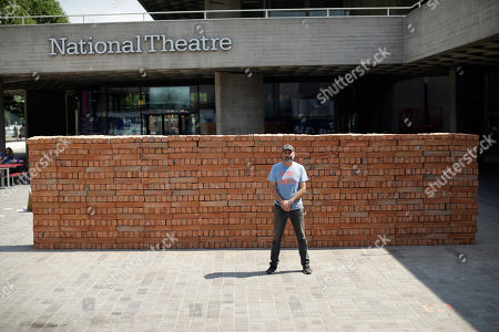 Mexican artist Bosco Sodi poses for photographs in front of his performative installation 'Muro' (wall), an 8 meter long wall in the riverside square of the National Theatre on the south bank of the River Thames in London, . The piece put up Saturday morning, made up of 1600 clay bricks made in Mexico, is his response to U.S. President Donald Trump's desire to build a wall along the Mexican-U.S. border. Later on Saturday passersby will be invited to dismantle the wall brick-by-brick and take part of the installation home