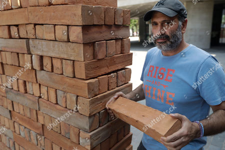 Mexican artist Bosco Sodi poses for photographs with a brick from his performative installation 'Muro' (wall), an 8 meter long wall in the riverside square of the National Theatre on the south bank of the River Thames in London, . The piece put up Saturday morning, made up of 1600 clay bricks made in Mexico, is his response to U.S. President Donald Trump's desire to build a wall along the Mexican-U.S. border. Later on Saturday passersby will be invited to dismantle the wall brick-by-brick and take part of the installation home