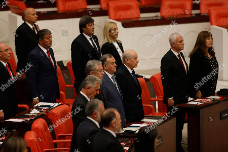 Devlet Bahceli, front row third right, leader of Turkey's Nationalist Movement Party, or MHP, along with other parliamentarians attend the opening session of the new parliament in Ankara, Turkey, following last month's elections that have shifted more power to the presidency. Turkey's governing system is changing from a parliamentary system to an executive presidency, which abolishes the office of the prime minister and changes parliament's responsibilities