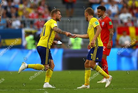 John Guidetti of Sweden passes notes from the bench to Sebastian Larsson of Sweden and his team mates