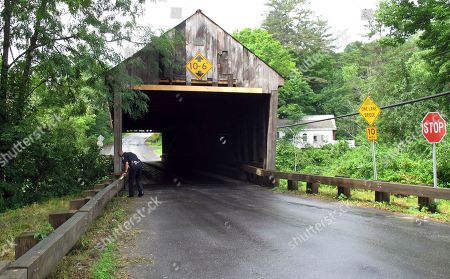 Police Chief Michael Evans stands near the Sayre's Covered Bridge over the Ompompanoosuc River in Thetford, Vt. In the last year, the bridge was repeatedly hit by over-height vehicles. Officials in communities that still rely on covered bridges as part of their local transportation networks have said that damage caused by modern vehicles is a vexing problem