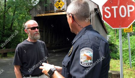 Stuart Rogers, left, chairman of the town select board, talks with Police Chief Michael Evans in front of the the Sayre's Covered Bridge over the Ompompanoosuc River in Thetford, Vt. In the last year, the bridge was repeatedly hit by over-height vehicles. Officials in communities that still rely on covered bridges as part of their local transportation networks have said that damage caused by modern vehicles is a vexing problem