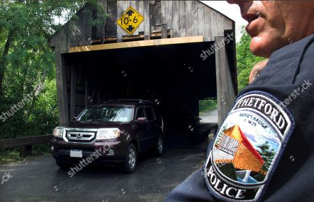Police Chief Michael Evans watches a vehicle exit the Sayre's Covered Bridge over the Ompompanoosuc River in Thetford, Vt. In the last year, the bridge was repeatedly hit by over-height vehicles. Officials in communities that still rely on covered bridges as part of their local transportation networks have said that damage caused by modern vehicles is a vexing problem