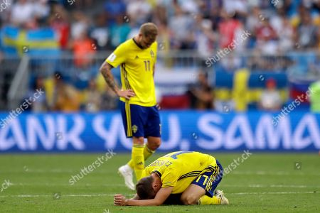 Sweden's Viktor Claesson, front bottom, and Sweden's John Guidetti react at the end of the quarterfinal match between Sweden and England at the 2018 soccer World Cup in the Samara Arena, in Samara, Russia