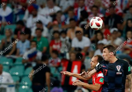 Croatia's Mario Mandzukic, right, jumps for the ball with Russia's Sergei Ignashevich during the quarterfinal match between Russia and Croatia at the 2018 soccer World Cup in the Fisht Stadium, in Sochi, Russia