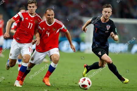 Russia's Roman Zobnin, left, Sergei Ignashevich, center, and Croatia's Ivan Rakitic run for the ball during the quarterfinal match between Russia and Croatia at the 2018 soccer World Cup in the Fisht Stadium, in Sochi, Russia