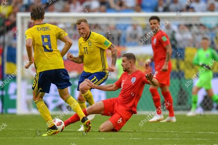 Jordan Henderson of England tackling the ball just in front of John Guidetti of Sweden at Samara Stadium during the quarter final between England and Sweden during the World Cup