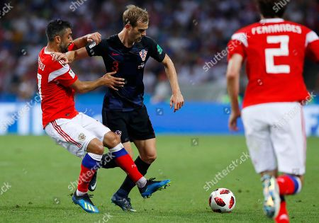 Russia's Fyodor Kudryashov, left, challenges for the ball with Croatia's Ivan Strinic during the quarterfinal match between Russia and Croatia at the 2018 soccer World Cup in the Fisht Stadium, in Sochi, Russia