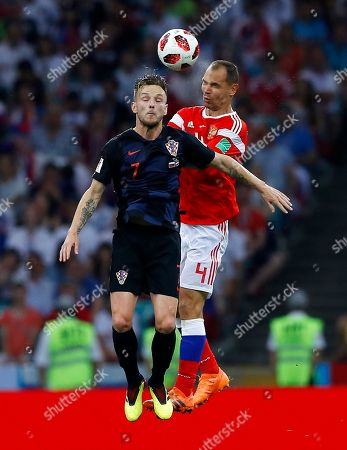 Croatia's Ivan Rakitic, left, jumps for the ball with Russia's Sergei Ignashevich during the quarterfinal match between Russia and Croatia at the 2018 soccer World Cup in the Fisht Stadium, in Sochi, Russia