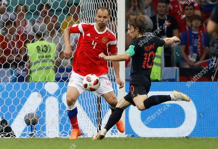 Croatia's Luka Modric, right, vies for the ball with Russia's Sergei Ignashevich during the quarterfinal match between Russia and Croatia at the 2018 soccer World Cup in the Fisht Stadium, in Sochi, Russia
