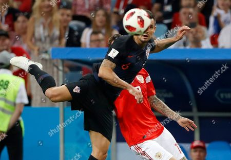 Croatia's Mateo Kovacic, front, vies for the ball with Russia's Yuri Gazinsky during the quarterfinal match between Russia and Croatia at the 2018 soccer World Cup in the Fisht Stadium, in Sochi, Russia