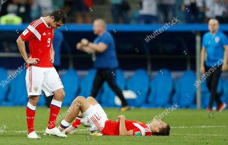 Russia's Alan Dzagoev, left, and Daler Kuziaev react after the quarterfinal match between Russia and Croatia at the 2018 soccer World Cup in the Fisht Stadium, in Sochi, Russia