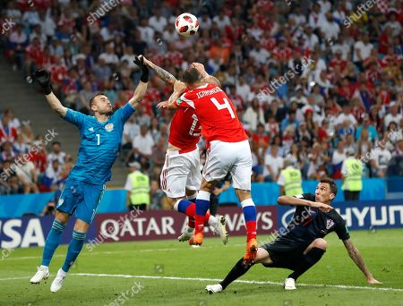 Croatia's Mario Mandzukic, right, watches Russia goalkeeper Igor Akinfeev, left, collide with teammates Sergei Ignashevich and Fyodor Kudryashov during the quarterfinal match between Russia and Croatia at the 2018 soccer World Cup at the Fisht Stadium in Sochi, Russia