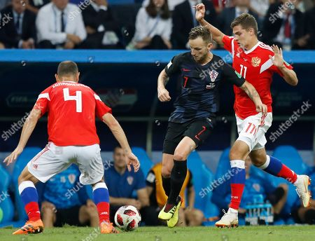 Russia's Sergei Ignashevich, left, Russia's Roman Zobnin, right, and Croatia's Ivan Rakitic challenge for the ball during the quarterfinal match between Russia and Croatia at the 2018 soccer World Cup in the Fisht Stadium, in Sochi, Russia