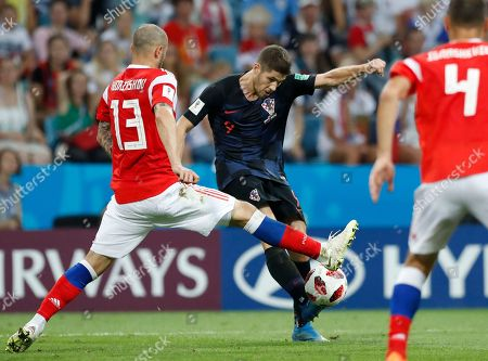 Croatia's Andrej Kramaric, right, kicks the ball ahead of Russia's Fyodor Kudryashov during the quarterfinal match between Russia and Croatia at the 2018 soccer World Cup in the Fisht Stadium, in Sochi, Russia
