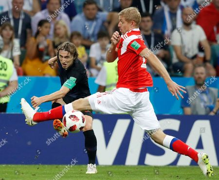 Croatia's Luka Modric, left, and Russia's Yuri Gazinsky challenge for the ball during the quarterfinal match between Russia and Croatia at the 2018 soccer World Cup in the Fisht Stadium, in Sochi, Russia