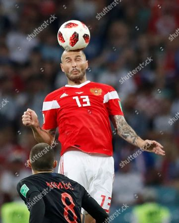 Russia's Fyodor Kudryashov jumps for the ball ahead of Croatia's Mateo Kovacic during the quarterfinal match between Russia and Croatia at the 2018 soccer World Cup in the Fisht Stadium, in Sochi, Russia