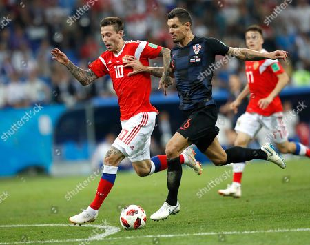 Russia's Fyodor Smolov, left, and Croatia's Dejan Lovren challenge for the ball during the quarterfinal match between Russia and Croatia at the 2018 soccer World Cup in the Fisht Stadium, in Sochi, Russia