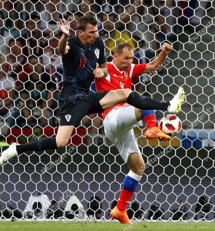 Croatia's Mario Mandzukic, left, and Russia's Sergei Ignashevich challenge for the ball during the quarterfinal match between Russia and Croatia at the 2018 soccer World Cup in the Fisht Stadium, in Sochi, Russia
