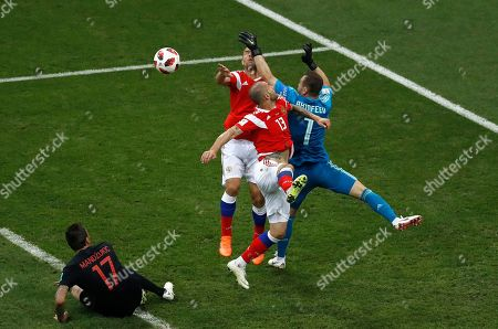 Stock Photo of Croatia's Mario Mandzukic, left, watches Russia goalkeeper Igor Akinfeev, right, collide with teammates Sergei Ignashevich and Fyodor Kudryashov, 2nd right, during the quarterfinal match between Russia and Croatia at the 2018 soccer World Cup at the Fisht Stadium in Sochi, Russia