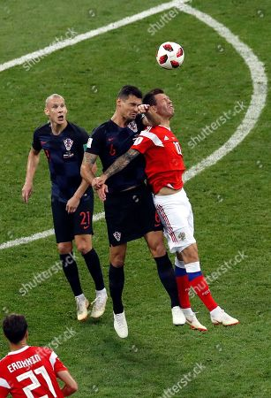 Croatia's Dejan Lovren jumps for the ball with Russia's Fyodor Smolov, right, during the quarterfinal match between Russia and Croatia at the 2018 soccer World Cup at the Fisht Stadium in Sochi, Russia