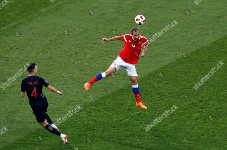Russia's Sergei Ignashevich heads the ball away from Croatia's Ivan Perisic, left, during the quarterfinal match between Russia and Croatia at the 2018 soccer World Cup at the Fisht Stadium in Sochi, Russia