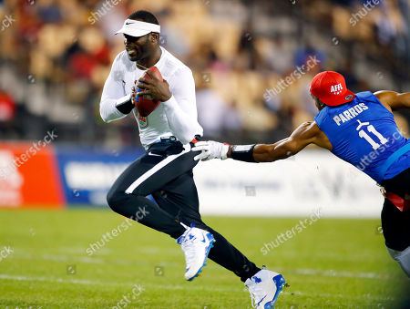 Ocho's Clayton Parros, right, reaches for the flag of Roadrunners' Michael Vick during a semifinal game against Ocho during the American Flag Football League (AFFL) U.S. Open of Football tournament, in Kennesaw, Ga