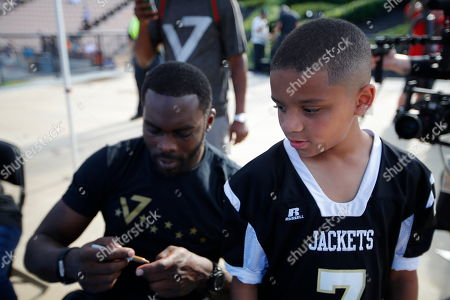 Michael Vick signs autographs before the semifinal round of the American Flag Football League (AFFL) U.S. Open of Football tournament, in Kennesaw, Ga